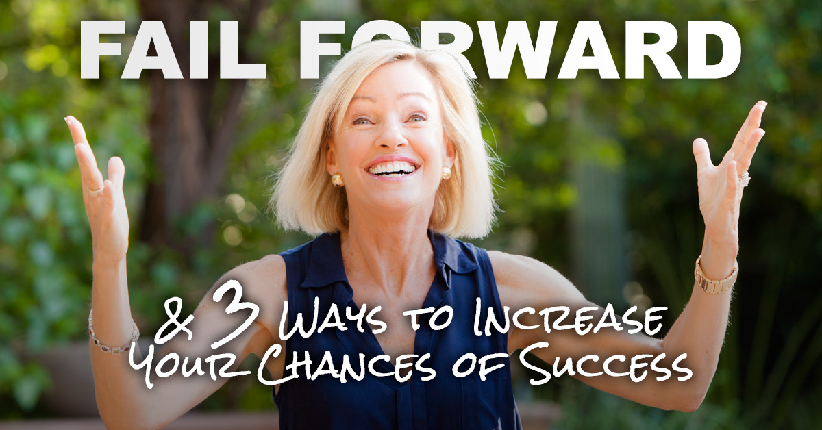 Kim Kiyosaki on staging holding up an empowered fist of encouragement for the audience